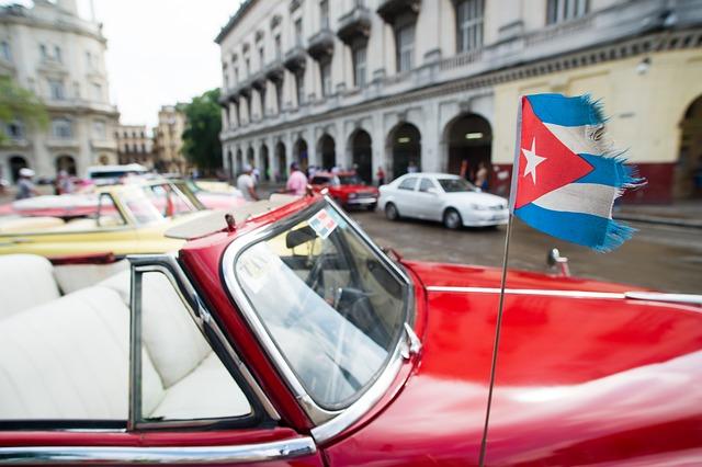 una vecchia auto cubana sulla quale sventola la bandiera del Paese