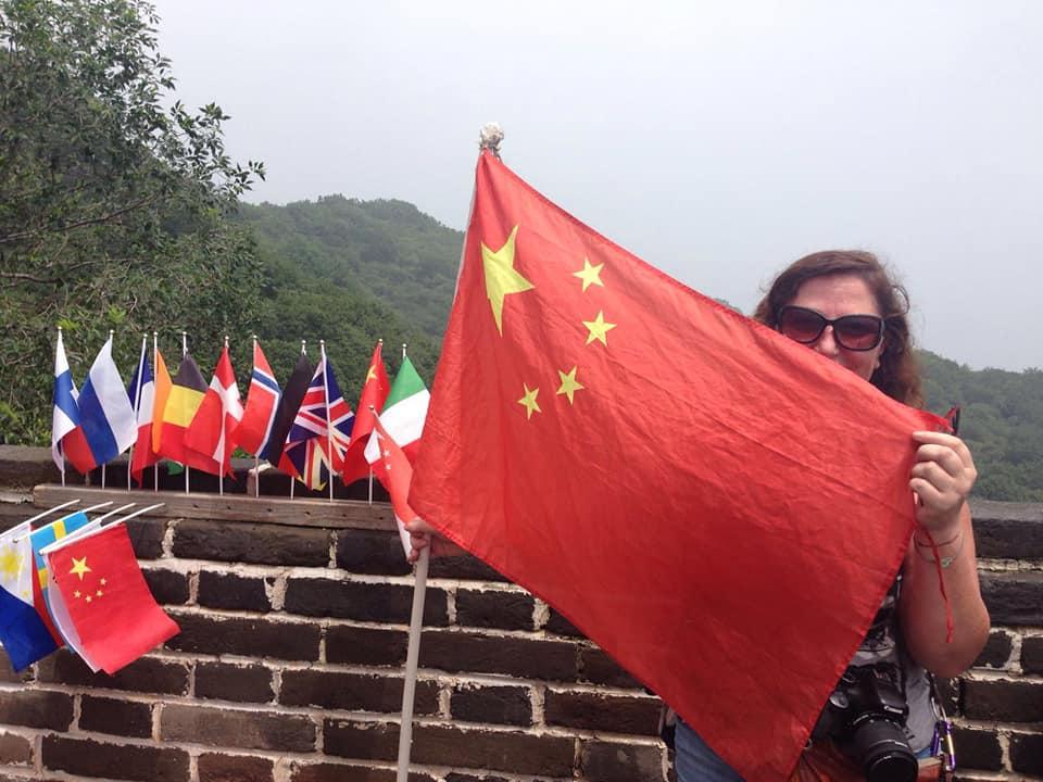 Simonetta Clucher con la bandiera sulla Grande Muraglia Cinese
