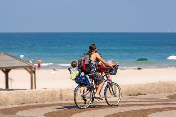 spiaggia di Tel Aviv donna in bici con i bambini